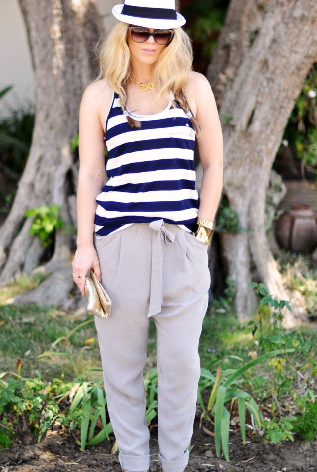 striped tank  and silk pants with  gold accessories and a hat