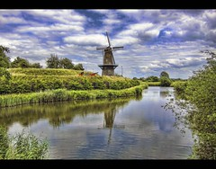"behind the watergate - windmill ""de hoop"" (Wim Koopman) Tags: sky mill reed water windmill grass clouds canon hoop reflections river de photography photo gate wind stock powershot dyke dike rijn watergate stockphoto s90 waal stockphotography s100 wpk s95"