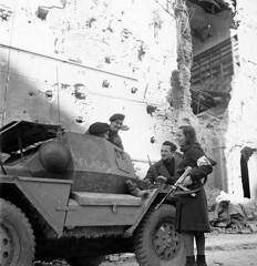 Two Canadian troops pause to get directions from Italian partisans near the village of Bagnacavallo sometime in Jan 1945. The young lady is armed with the good ole Thompson SMG. The armored car is a Dingo Mk I made in Australia (the Canadians called it the Lynx).