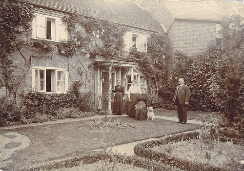 Family and dog in their garden at home. 1900s