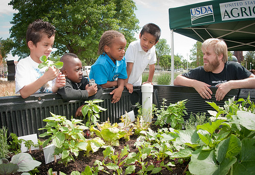 Stephen Kendall, Food Donations Coordinator at DC Central Kitchen, and students from Powell Elementary School in NW, DC hunt for  herbs in the Truck Farm during the USDA Farmers Market and the official kick off of the People's Garden Friday activities on Friday, June 3, 2011 in Washington, DC.