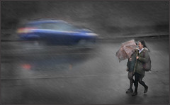 Laughing in the Rain (rogermccallum) Tags: rain umbrella girls schoolgirls laughing car bluecar speed weather raining
