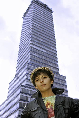 Person in leather jacket standing in front of tall building wearing a gold crown made of wire-like material.