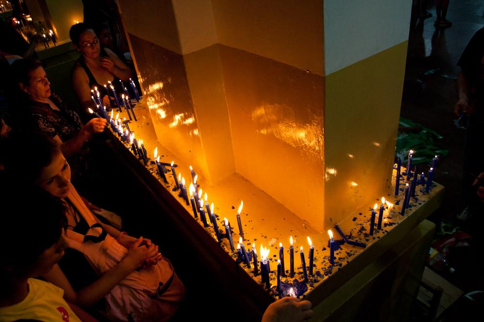 Gente devota enciende y deposita sus velas en los pilares de la Capilla bajo la Basílica, hacen sus oraciones y luego continúan su camino. Miles de peregrinos realizan esta tradición cada año para llevar a sus vidas una nueva promesa o la alegría de haber pagado por los favores recibidos.  (Elton Núñez - Caacupé, Paraguay)