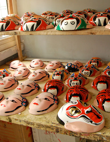 Dozens of colorful masks drying on shelves