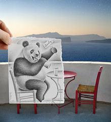 Pencil Vs Camera - 41 (Ben Heine) Tags: pencilvscamera imaginationvsreality drawingvsphotography illusion art benheine series hand main paper papier creative panda animal wild cute alcoholism drink beer wine landscape addiction drug waterscape dessin sketch croquis fantasy humor table chairs chaises greece santorini horizon evening soir contrast sea mer ocean hold alone desperate ivre saoûl loneliness sad sadness suicide couple love amour divorce separation sweet mignon extinction expressive kunst theartistery samsungimaging ours bear massive fat depression holidays lovely alibi guilty cry oia scenery island