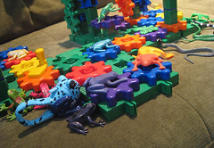 colorful rubber/plastic frogs and snakes on and around a system of colorful gears