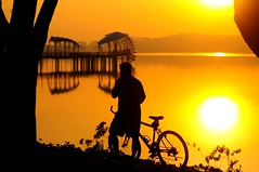 Quiet Enjoyment (Trim Reaper) Tags: park sun man reflection water bicycle silhouette sunrise nikon singapore reservoir nikkor 70300mm d90 lowerseletar
