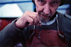 blacksmith and his jewellery (perminna) Tags: christmas portrait color film handmade availablelight iso400 craft nikonf100 jewellery products 135 blacksmith pushed nikkor oulu analogphotography wideopen tradefair c41 homedeveloped 35mmf2d fujipro400h diycolor epsonv700 2stops rolleidigibase 400at1600 pohjankartano annualwomensfair