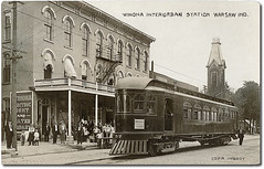 """""""Winona Flyer"""" at Winona Interurban Station, Warsaw, Indiana (Hoosier Recollections) Tags: girls people woman usa signs man men history industry boys station kids buildings walking advertising children awning hardware clothing women crowd indiana streetscene machinery transportation shops pedestrians warsaw depot cigars storefronts interurban trolleys businesses realphoto kosciuskocounty hoosierrecollections"""