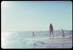lets do this more often (kodachrome series #2) (Douglas E Pope) Tags: blue light shadow sea sky woman sun reflection bird love film beach girl hair bottle sand doll pretty seagull cider slide siena kodachrome shillouette horizen exa1b autaut