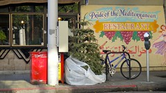 Xmas Tree Parking, San Francisco (Lynn Friedman) Tags: sanfrancisco street xmas blue red food tree bike bicycle sign st bag restaurant mural published mediterranean middleeast arabic rack sutter meter parkingmeter fillmore curb bikerack newspaperstand cusine pacificheights attribution magazinestand lightpoll lowerpacificheights lynnfriedman upperfillmore prideofthemediterranean friedmanlynn