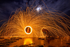Fire! (raluca_buzoianu) Tags: constanta romania abstract circle clouds fire fireworks human light lightpainting lights lighttrails longexposure men moon night nightphotography people persons reflection rocks seaside shore sparks spin steel steelwool trails umbrella water wire
