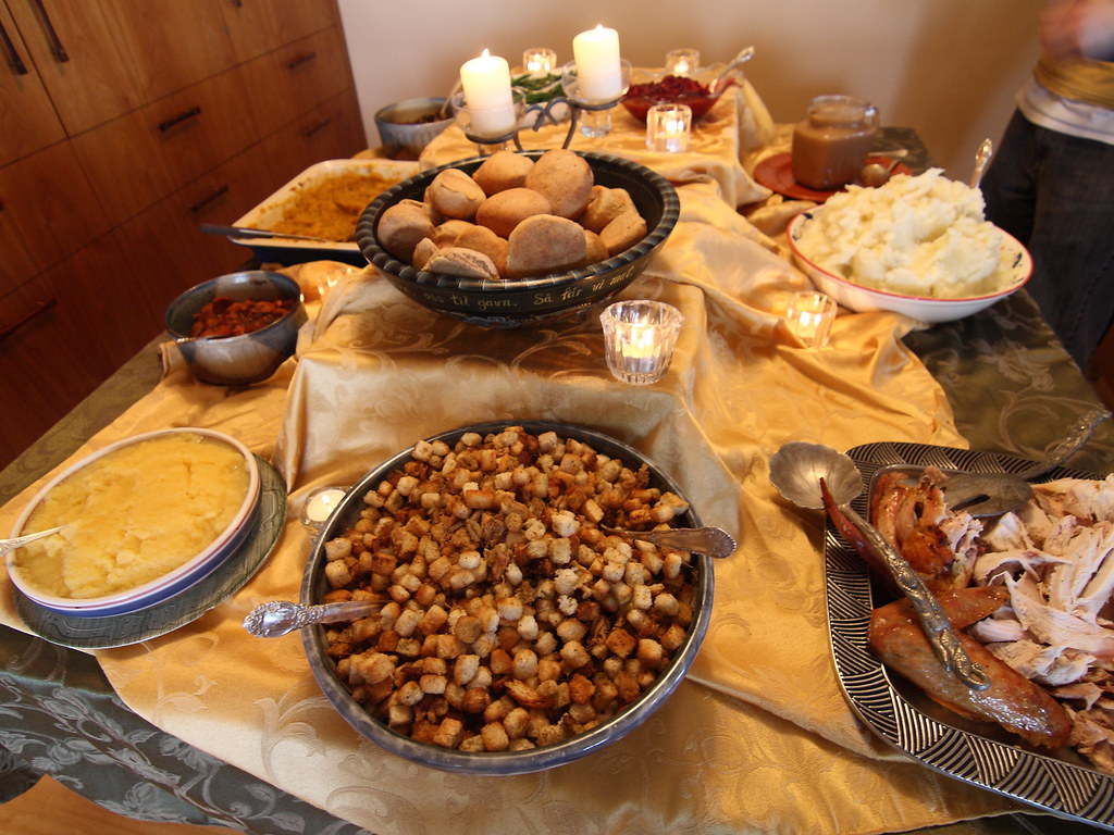 Table with many Thanksgiving dishes.