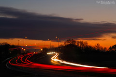 Traffic light trails on the A1 Cambridgeshire (Nigel Blake, 12 MILLION...Yay! Many thanks!) Tags: lighting street light sunset red sky white motion blur cars lamp corner canon photography evening movement long exposure traffic post bend time dusk tripod trails cable lamppost rush hour trucks rushhour a1 curve blake timer nigel cambridgeshire gitzo eos1dsmkiii