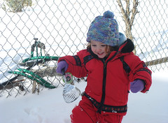 Speck in red snowsuit with play shovel in hand and grin