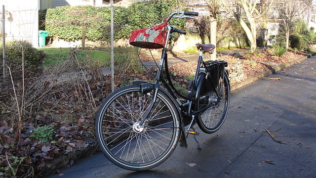 Photograph of my Dutch bike with a red cloth-wrapped container of Christmas cookies tied to the handlebars