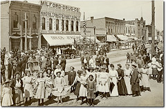 Crowd of people celebrating a holiday, Milford, Indiana (Hoosier Recollections) Tags: street girls people woman signs man men history cars boys kids buildings walking advertising children real awning photo clothing cafe women general crowd hats restaurants scene flags parade bicycles celebration transportation drugs shops pedestrians storefronts automobiles businesses wagons barbers jeweler kosciuskocounty hoosierrecollections