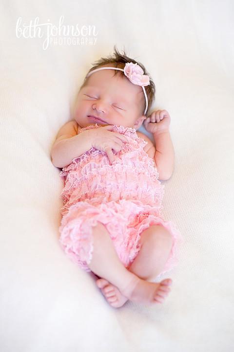 newborn baby in pink romper