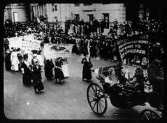 Women in horse-drawn carriage and on foot  mar...