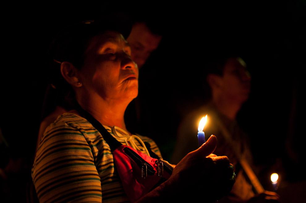 Una señora realiza su oración a la Virgen de Caacupé con vela encendida durante la Vigilia de Oración frente a la Basílica de Caacupé aguardando la hora festiva del 8 de Diciembre. (Elton Núñez - Caacupé, Paraguay)