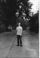 balloons don't make very good umbrellas (cavale) Tags: road portrait blackandwhite bw 3 man silly guy film wet rain weather orlando student sam boots florida kodak balloon tshirt dude prints miserable badweather soaking trix400 photoi rcpaper valenciacommunitycollege orlandoset cavalephotonet onedreadlock ilfordglossyrc