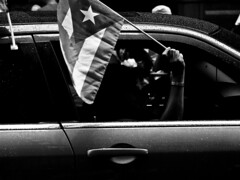 Anonymous Flagbearer (EcstaticAperture) Tags: nyc shadow blackandwhite bw ny newyork monochrome car silhouette contrast digital fuji puertorico manhattan flag highcontrast parade procession patriotism anonymous blackdiamond greyscale puertoricandayparade fujis9100 bhphotoleicastreetphotographycontest anonymousflagbearer