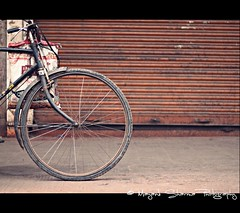 The wheel of progress (Mayank Sharma renewed :D :D) Tags: red orange india man bicycle wheel canon bag iron floor market steel delhi earlymorning streetphotography rubber cycle shutter tyre milkman chandnichowk