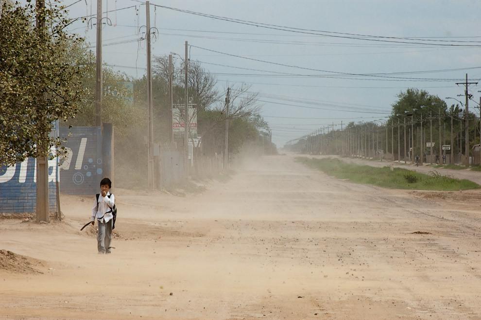 Soportando el viento y el polvo del terreno árido, un niño camina de regreso a su casa luego de la jornada escolar sobre una de las doble avenidas aún de tierra en la zona central de la Ciudad de Loma Plata. (Elton Núñez - Loma Plata, Paraguay)