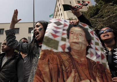 A pro-Gadhafi protester carries a picture of Libyan leader Moammar Gadhafi and chants anti-U.N. slogans as demonstrators block the path of UN Secretary-General Ban Ki-moon, unseen as he was leaving the Arab League headquarters on his way to Tahrir Square. by Pan-African News Wire File Photos