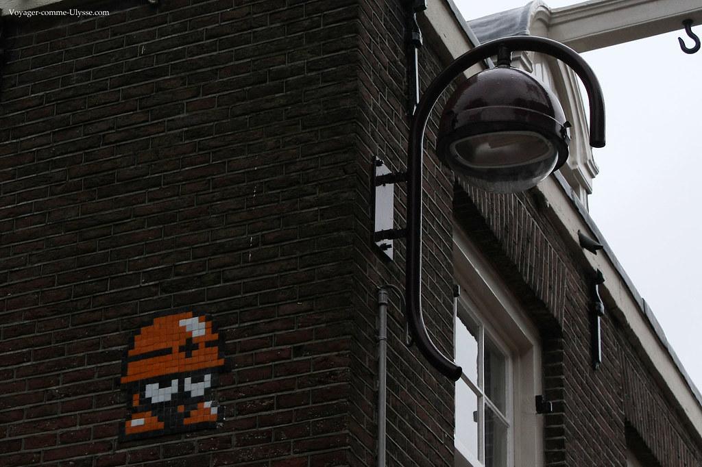 Lampadaire accroché au mur d'un immeuble. Remarquez le petit personnage décoratif en mosaïque.