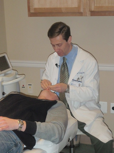 Dr. Adam Sobel prepares the patient's face for an Isolaz acne laser treatment demonstration by CosmopolitanSkinCareSolutions
