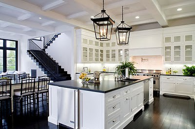 meridith_baer_spanish_style_house_home_kitchen_white_cabinetry_glass_front_uppers_island_dark_wood_floors_black_counters_countertops