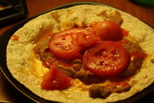 tortilla with refried beans, cheese, tomatoes, hot sauce