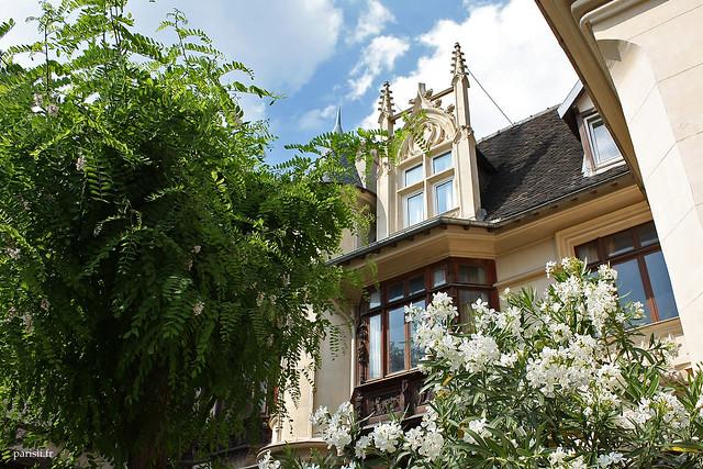 Un immeuble néo-gothique, caché discrètement derrière un jardin