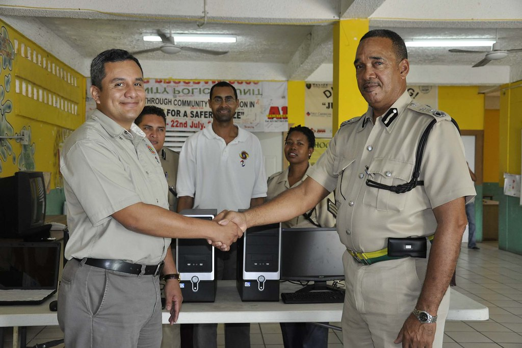 YFF COMPOL Crispin Jeffries receives computers from Mr Daniel Cano, SIF Executive Director
