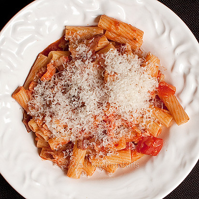 overhead shot of pasta with tomato and bacon garnished with Parmesan cheese