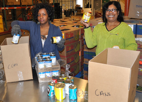 Southwest Region SNAP staffers Katrina Kamau and Vernzel Mosby-Byrd  box canned goods during a volunteer evolution at the North Texas Food Bank in Dallas. The North Texas Food Bank provided access to over 45 million meals in 2010.