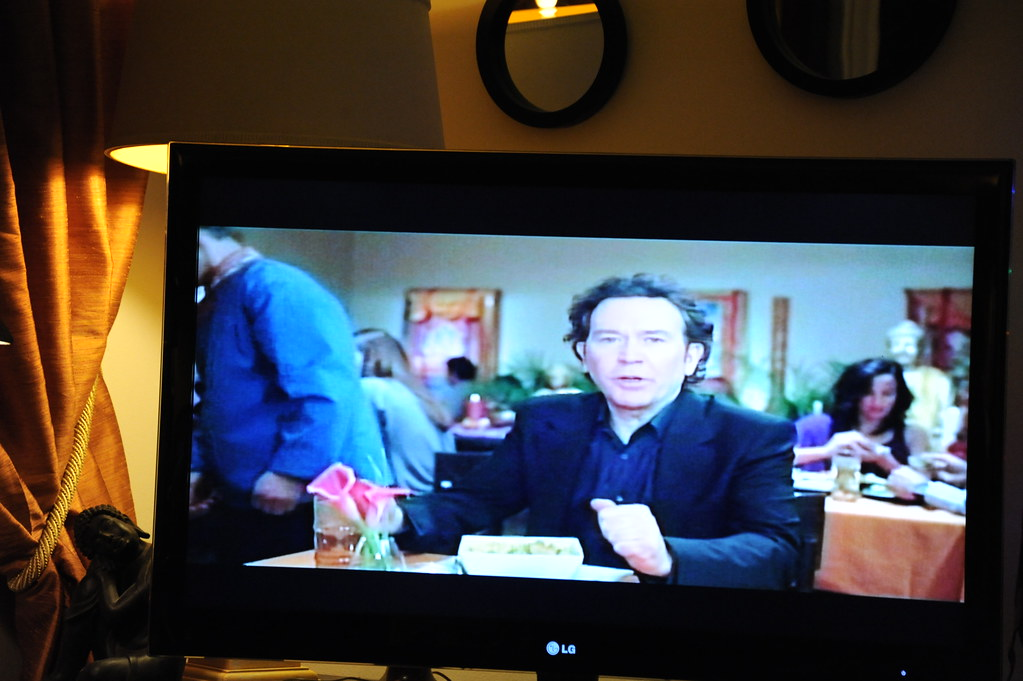 Buddhism in American Culture: Super Bowl ad, with Timothy Hutton, Tibetan Buddhist restaurant, Buddha statue, thangkas, flowers, TV, mirror, lamp, Buddha statue, gold curtains, Seattle, Washington, US