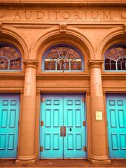 Pillars (bluesundrops) Tags: cameraphone street nyc blue windows urban orange ny newyork doors greenwich torch pillars auditorium greenwichvillage