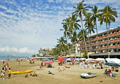 On A Beach (Serge Freeman) Tags: vacation sky people beach palms mexico sand puertovallarta hotels umbrellas