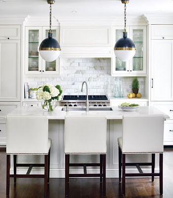 hen_white_nailhead_trim_barstools_cararra_marble_subway_tile_backsplash_hick_pendant_lights_blue_gold_crown_molding_top_cabinets_dark_wood_floors