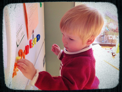 Jacob arranges letters on the fridge