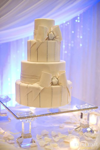 wedding cake with bow and rhinestone glass cake stand