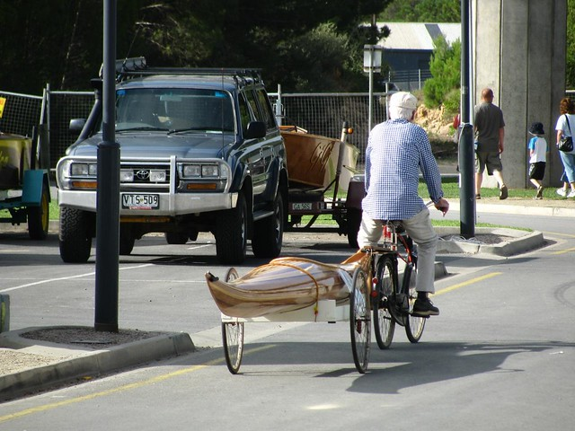 Strip planked kayak being towed behind a bicycle - boat and bicycle trailer