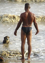 Who's the master? (Legin_2009) Tags: ocean sea dog man black male men guy beach wet water standing stand back surf waves african guys barefoot males slip caribbean mann speedo mec herren mecs mannes unterwsche