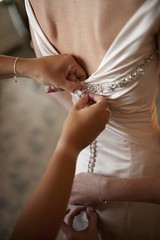 [Wed2K10] Putting on the Dress (kisluvkis) Tags: wedding dress buttons bracelet gettingready pfister editorialphotography girlsgettingready thepfister 05womengettingready frontroomphotography frphotocom lakeparkbistroweddingphotographer neilcalfa wed2k10 onegoodluv