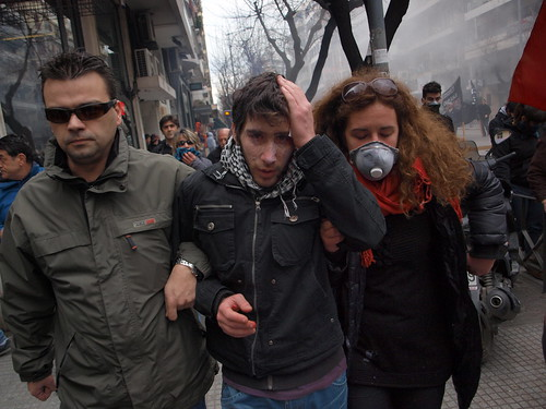 Injured Greek marcher helped by protesters after police attack.