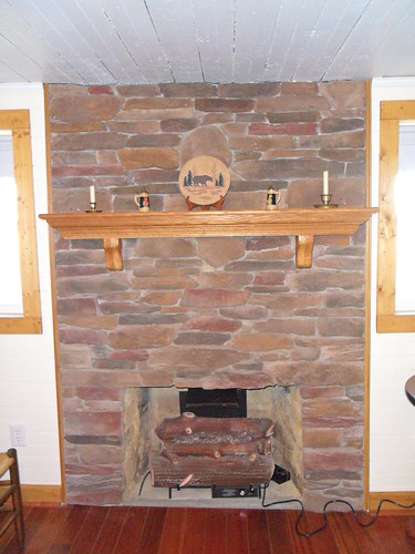 natural stone fireplace with wood mantle made in traditional masonry style