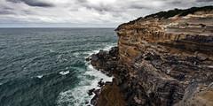 Rugged Coastline (J.Shultz Photography) Tags: ocean new sea cliff water rock wales clouds coast sandstone rocks waves moody crash south dramatic australia nsw newsouthwales coastline geology aus southcoast clifs